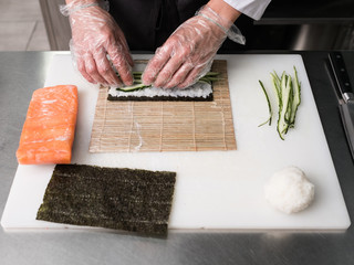 I bet it tastes delicious. Chef prepares sushi rolls from fresh ingredients - rice nori salmon and cucumber.