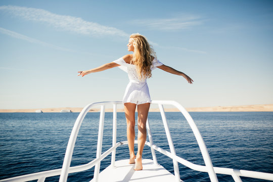 Woman standing on the nose of the yacht at a sunny summer day, breeze developing hair with open arms beautiful sea on background