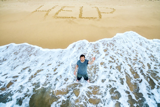 Castaway and lost in uninhabited island, survivor is calling for help on deserted beach