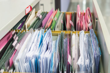 files document of hanging file folders in a drawer in a whole pile of full papers, the concept