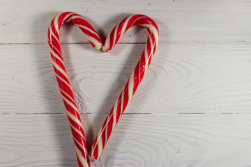 Two holiday candy canes in the shape of a heart on white wooden table