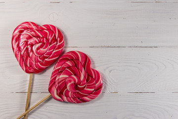 Two heart shaped lollipop on white wooden background