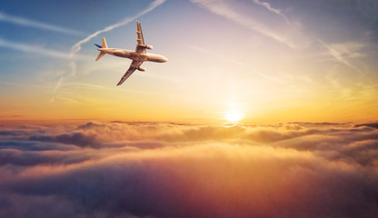 Commercial airplane jetliner flying above clouds in beautiful sunset light. Fototapete