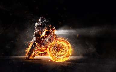 Dark motorbiker staying on burning motorcycle, separated on black background.
