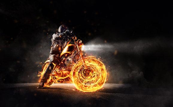 Dark motorbiker staying on burning motorcycle, separated on black background.