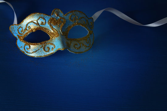 Image of elegant blue and gold venetian, mardi gras mask over blue background.