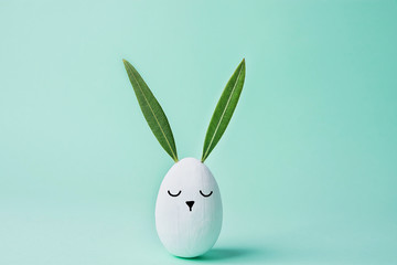 Decorative White Painted Easter Egg Bunny with Drawn Cute Kawaii Face. Green Leaves as Ears. Pastel Turquoise Background. Spring Holiday Crafts Kids Concept. Greeting Card Poster Banner. Copy Space