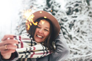 Stylish smiling woman wearing hat, scarf and coat hold bengal fire in hand among winter landscape and snowy forest. Boho style. Winter holidays