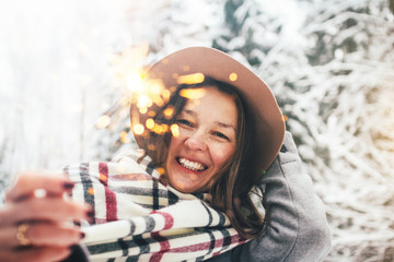 Pretty young woman hold bengal flight in hand among snowy landscape and have fun in winter holidays. Boho girl enjoying sparkler in her hands. Wearing coat, plaid scarf and vintage hat