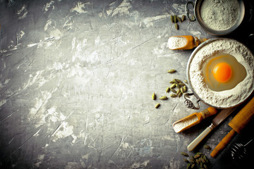 Dough with flour on an old background in a composition with kitchen accessories
