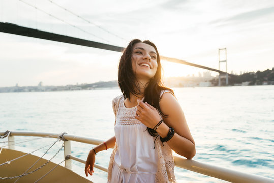 A beautiful Latin girl on a yacht sails under a modern bridge at sunset and laughs