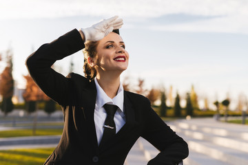 happy beautiful stewardess girl in uniform waiting for her flight, looking at the sky