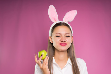 distressed girl in pink ears holding an apple