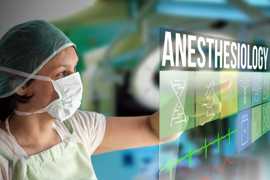 Anesthesiology concept. Doctor using a futuristic touch screen concept computer with medical icons on it. Healthcare operation surgery room on background.