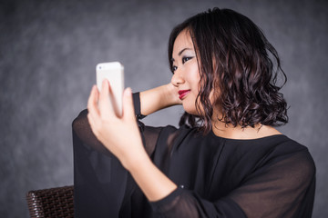 young asian woman making selfie on gray background