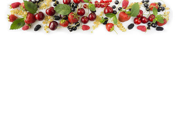 Ripe strawberries, redcurrants, blackcurrants, mulberries, raspberries and cherries on white background. Berries at border of image with copy space for text.