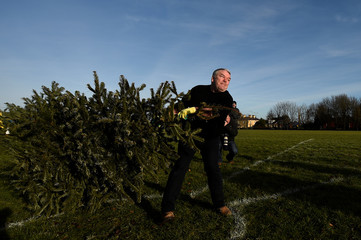 A man participates in a Christmas tree throwing competition, in the County Clare town of Ennis