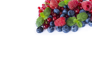 Red-blue food on a white. Ripe blueberries, red currants, raspberries with mint on a white background. Mixed berries with copy space for text. Red and blue berries.