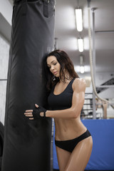 Beautiful young adult girl posing happy with boxing bag.