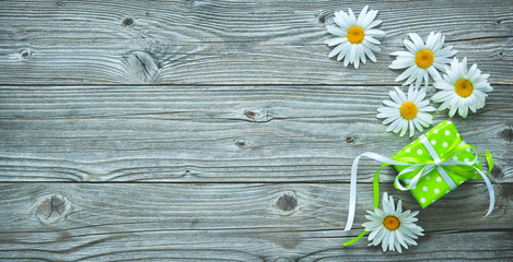 Gift box and daisy flowers on old wooden planks