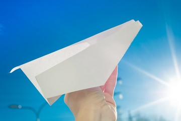 Abstract paper plane, in hand, sky, sun background
