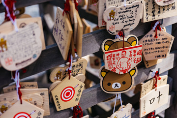 Close up Ema are small wooden plaques, common to Japan, in which Shinto and Buddhist worshippers write prayers or wishes in Hokkaido Shrine in Sapporo. Hokkaido, Japan.