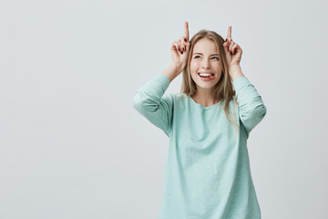 Positive funny European woman with blonde dyed hair dressed in blue sweater smiling broadly holding fingers above head, playing with her beloved child. Happiness and motherhood