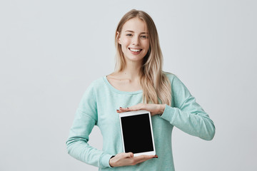 Portrait of young beautiful smiling blonde female holding and showing blank tablet computer with copy space for your text, looking pleasantly at the camera isolated against gray background
