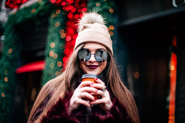young stylish girl in a burgundy coat and a knitted hat holds coffee and smiles. dressed in sunglasses smiling at the camera
