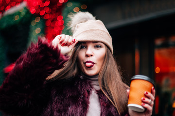 Portrait  girl with long hair in Burgundy fur coat of artificial fur knitted hat and bright burgundy lips walking on street with coffee to go looks into the camera of fools and shows the language