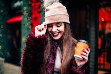 Portrait pretty girl with long hair in Burgundy fur coat of artificial fur knitted hat and bright burgundy lips She looks excited to camera City lifestyle