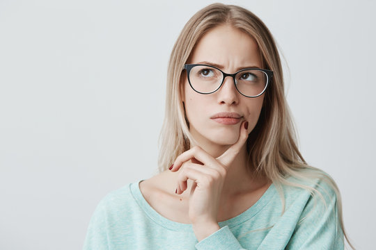 Indoor shot of thoughtful pretty woman has long blonde hair with stylish eyewear, looks aside with pensive expression, plans something on coming weekends, poses against blank wall. Puzzled female