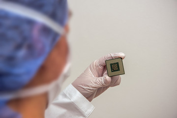 Female laboratory coworker holds in hand a digital CPU processor microchip in a lab. Electronic engineer is wearing protective clothing. Concept: computer and technology or computer security