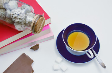 tea and chocolate on the table with book and potpourri