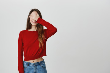 I don't see anything. Close up of funny joyful caucasian girl with long dark hair in stylish clothes smiling with teeth, clothing eyes with hand, waiting for birthday present from friends