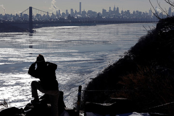 A woman photographs ice on the Hudson River, with the George Washington Bridge and New York City in the background, from the Rockefeller Lookout in the Palisades Interstate Park in Englewood