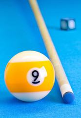 Billiard pool game nine ball with chalk and cue on billiard table