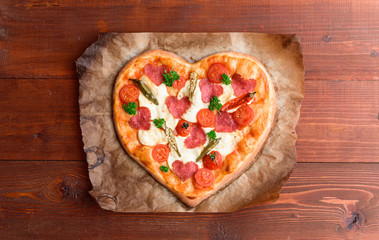 the chef makes a pizza heart for the Valentine's Day holiday. classic Italian pizza with salami and mozzarella