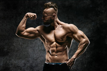 Naked strong man showing his biceps on dark background. Strength and motivation.