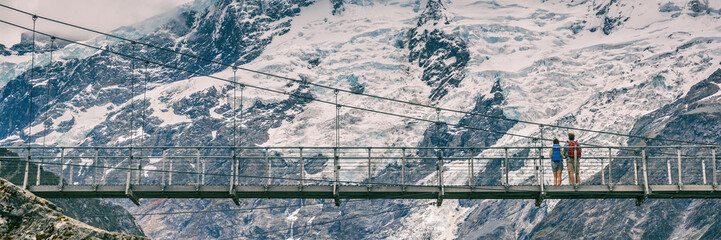 Hooker Valley Track hiking trail, New Zealand. Panoramic crop of bridge across the Hooker Valley track, Aoraki, Mt Cook National Park with snow capped mountains landscape. Banner crop.