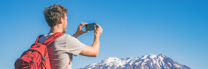 Travel tourist hiking man taking picture with phone of mountains landscape on summer hike adventure. Panorama banner with copy space on blue sky background.