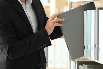 Young man taking folder with documents from shelf in archive