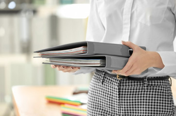 Young woman with documents in office