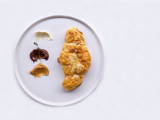 Traditional French breakfast croissant with almonds, chocolate, peanut butter on a white plate, On white table.