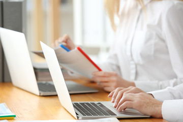 Young employees working with laptops and documents in office, closeup