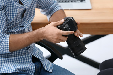 Young professional photographer with camera in office