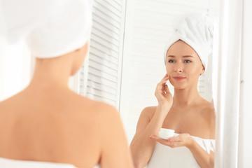 Young woman applying facial cream in bathroom