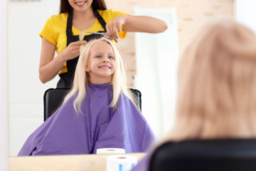 Female hairdresser working with little girl in salon