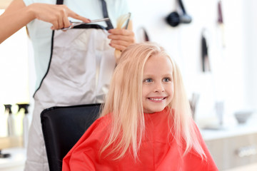 Female hairdresser working with little girl in salon, closeup
