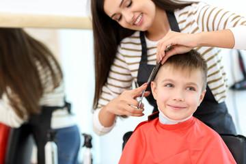Female hairdresser working with little boy in salon, closeup